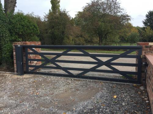 Aluminium sliding 5 bar gate in textured anthracite, with a naked nice motor hidden in the upright post, installed in Poulton