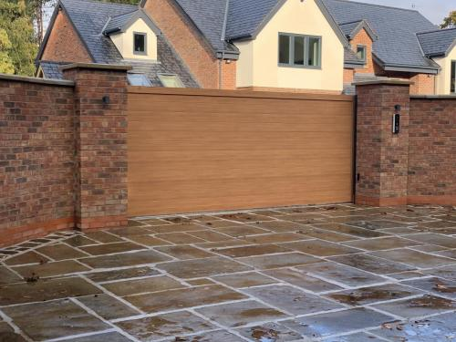 Sliding aluminium gate in golden oak installed in Cheshire