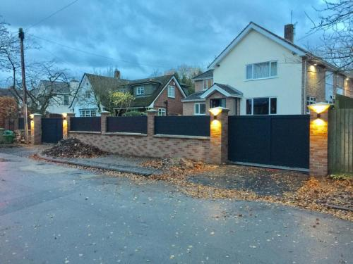 Aluminium sliding gates and matching fencing in anthracite with access control and lights installed in Wilmslow