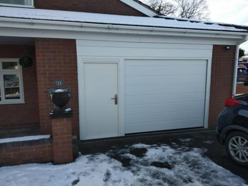 Insulated sectional garage door in white, medium rib with insulated security door, all mounted in a aluminium subframe with insulated top panel, installed in Kinnerton