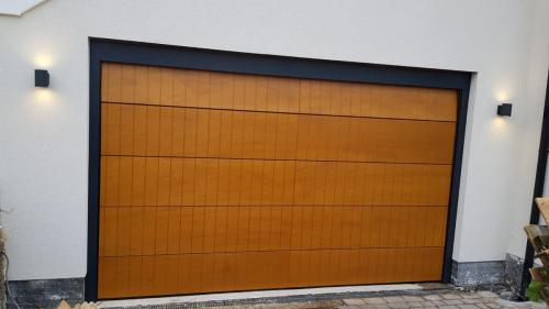 Insulated sectional garage door clad with Okume wood in an oak finish, installed in Blundell Sands